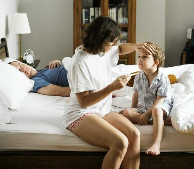 Mother Checking Child's Temperature During Cold and Flu Season